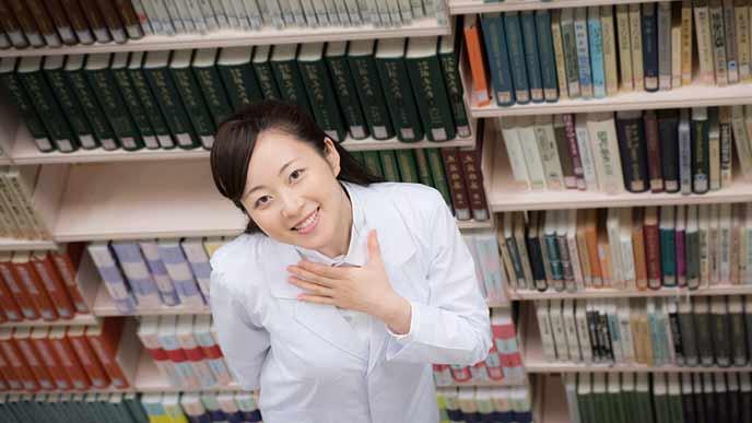 専門書の書棚の前に立つ大学院生