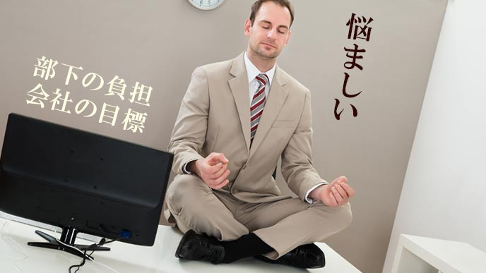 会社のデスクの上で座禅を組む中間管理職の男性