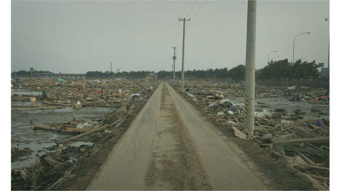 東日本大震災で被災した道路と両脇の瓦礫