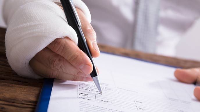 怪我をした手で書類を書く