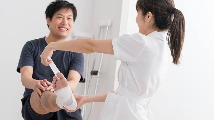 病院で足に包帯を巻かれる男性