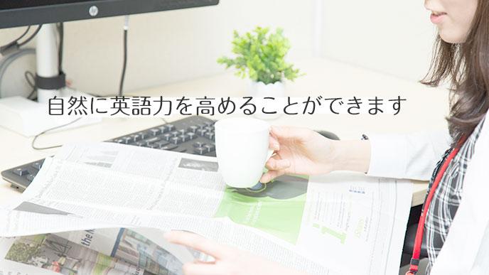 コーヒーの飲みながら英語の新聞を読んでいる女性