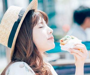 店外で食べる女性