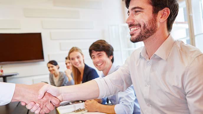 社内会議で上司と握手する会社員