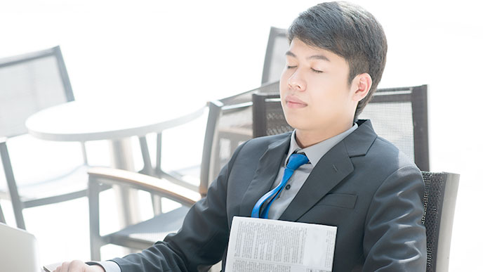 机で昼寝をする男性