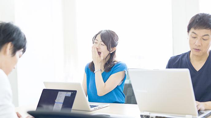 ノートパソコンの前にあくびをする女性社員