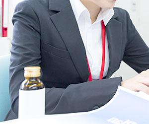 女性社員と栄養ドリンク