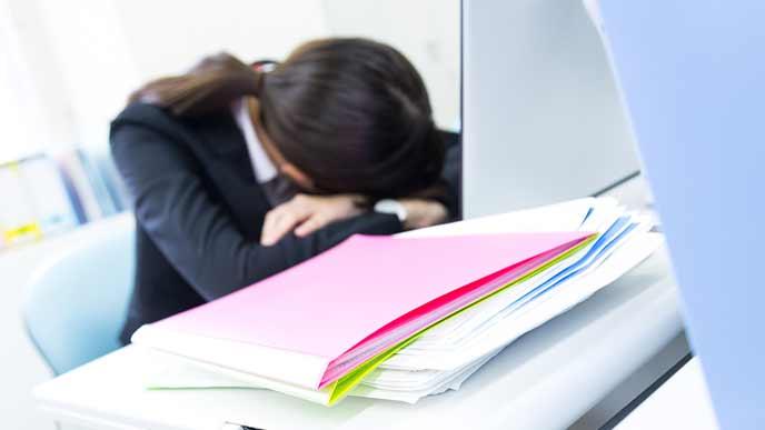 会社のデスクで腕枕をして寝る女性社員