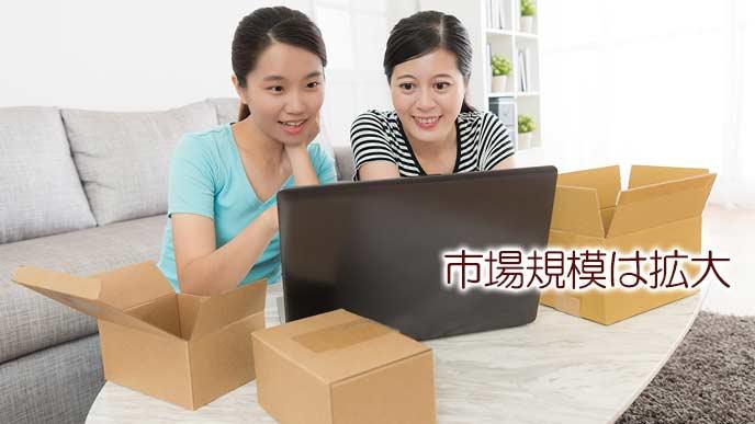 PC画面を見ながら荷物の梱包準備をする女性達