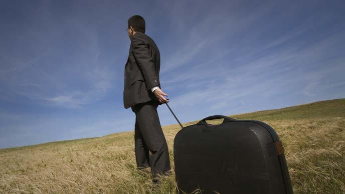 スーツケースを引きずりながら荒野を進むスーツ姿の男性