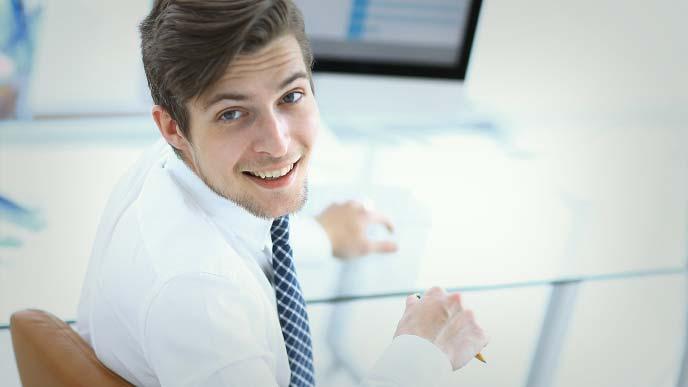 笑顔で振り向くデスクに座った男性