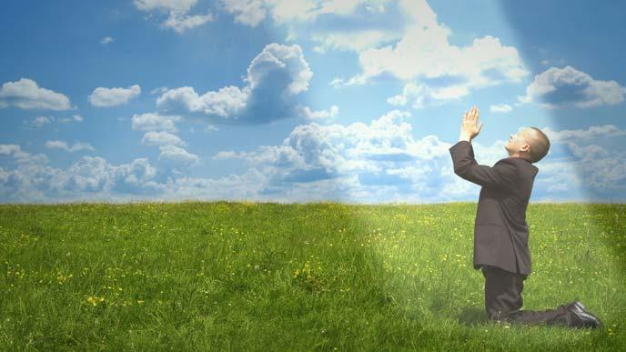 草原で祈るスーツ姿の男性に差し込んだ一筋の光明