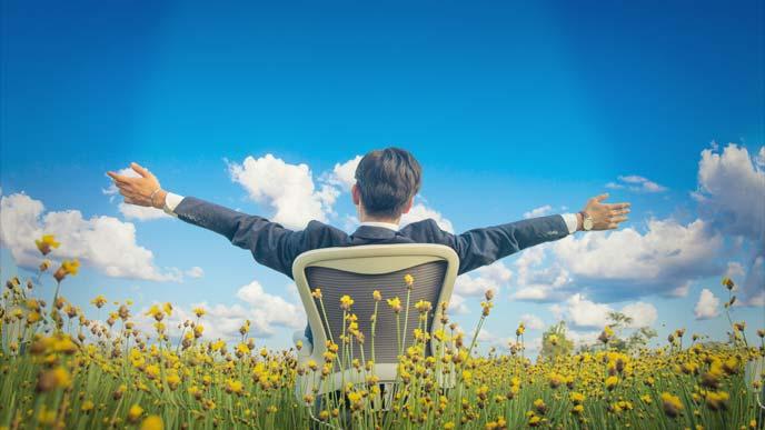 草原で光を浴びながら大きく腕を開く、オフィスチェアに座ったスーツの男性の後ろ姿