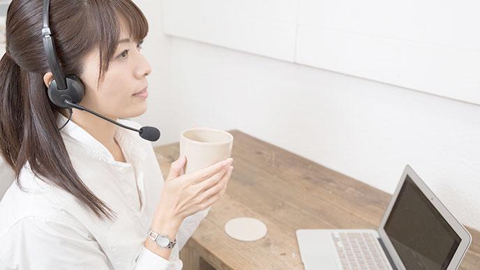 コーヒーを飲みながら働くヘッドセットを耳にかけた女性