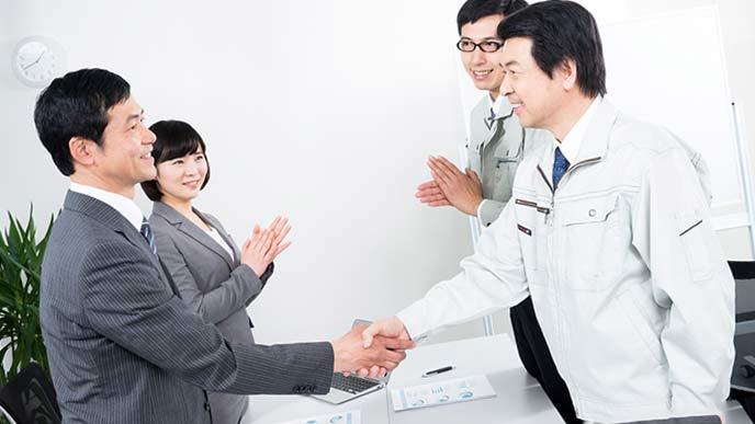 中小企業の経営者と銀行員が握手する