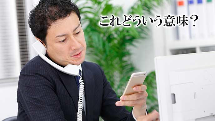 メールの文面を見ながら電話で質問する上司
