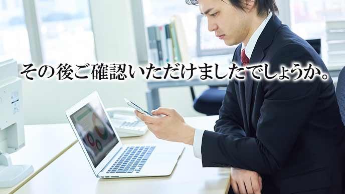 会社のデスクでPCとスマホを同時に見る男性