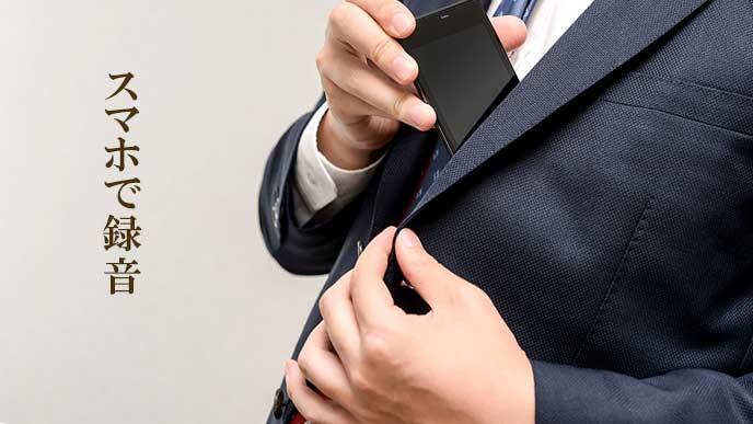 背広の内ポケットにスマホを入れる男性