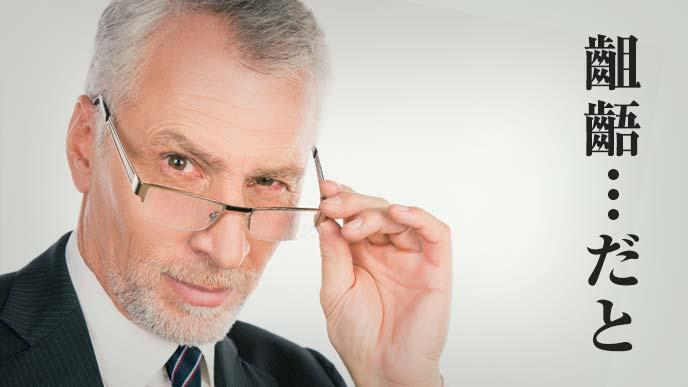 部下に齟齬と言われムッとした表情の眼鏡をかけた年配の男性
