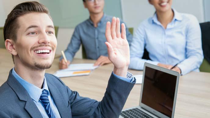 会議中明るく挙手する男性