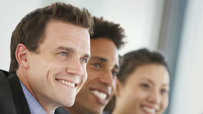 会議の席でポジティブな態度で話を聞く男性