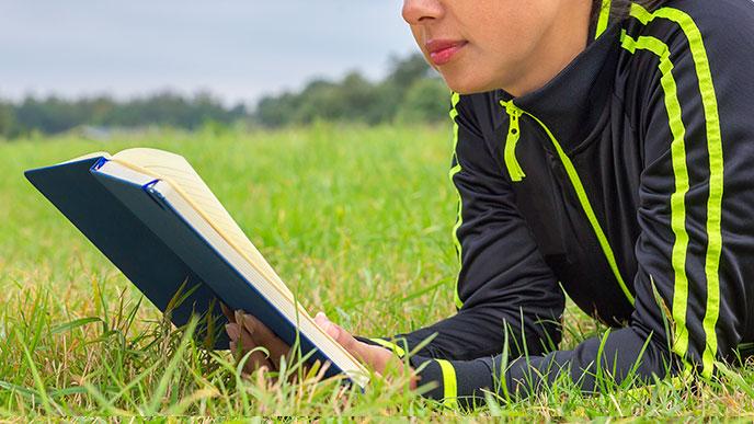 ラニング後にお外で本を読む女性