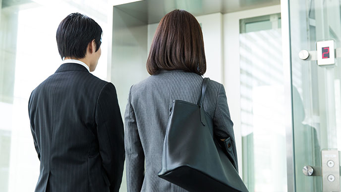 エレベーターが来るのに待つ社員