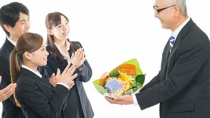 派手すぎない色の花束を定年退職者に渡す