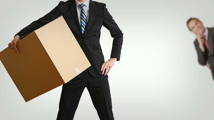 腰に手を当て足を開き段ボールを抱えるスーツ姿の男性