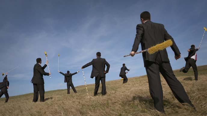 箒をもって草原で動き回る沢山のスーツ姿の男性