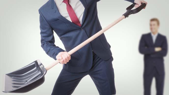 スコップを持って働くスーツ姿の男性