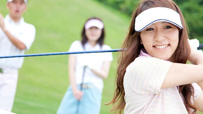 ゴルフをする女性と仲間
