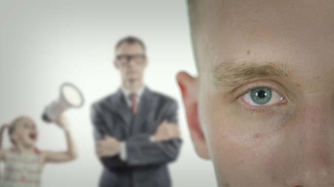 男性の冷たい瞳のアップと背後にぼんやり写る無表情な男性と男性に絡む幼女