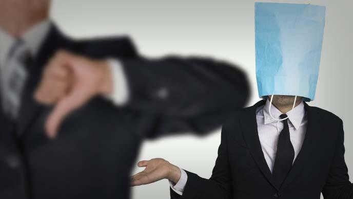 袋をかぶってお手上げのスーツ姿の男性と前景でサムズダウンする男性