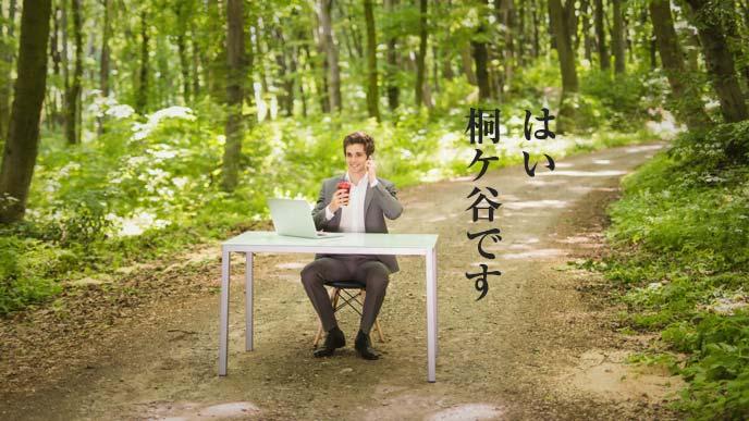 林道に置かれたパソコンデスクで電話に出る男性
