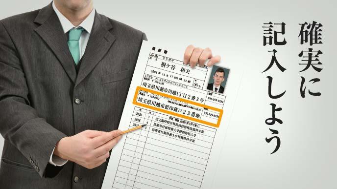 履歴書のサンプルを持ち鉛筆で指し示す男性