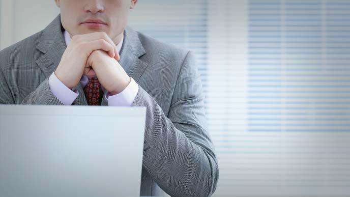 机に肘をついて考えるスーツ姿の男性
