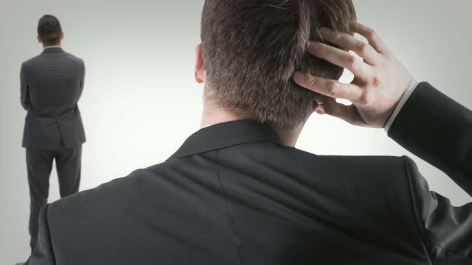 上司の後ろ姿を眺めながら頭をかく後ろ姿の男性