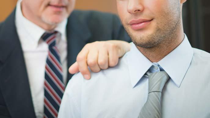 ホワイトカラーの男性の肩に手を置く年配の経営者