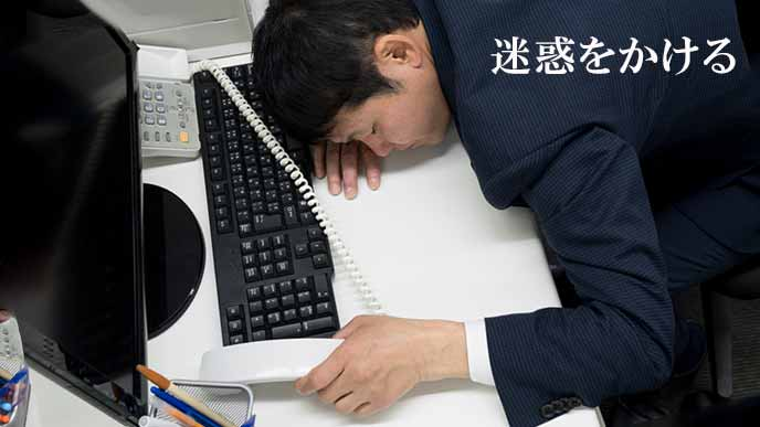仕事中にデスクに倒れる会社員