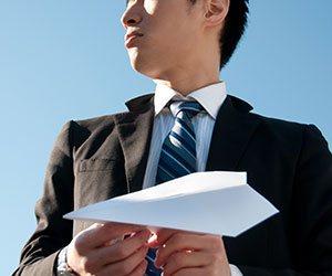 紙飛行機を飛ばそうとする男性社員