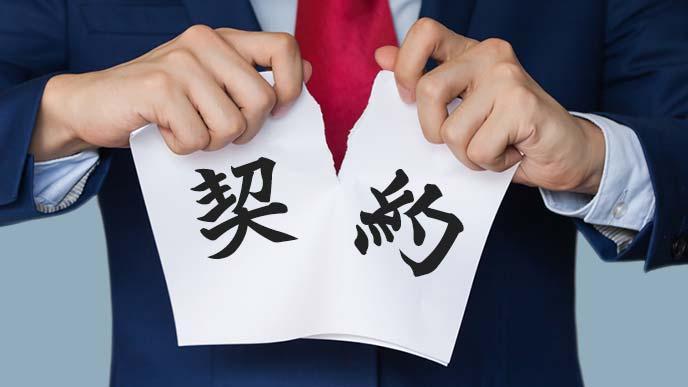 契約と書かれた紙を破くスーツ姿の男性