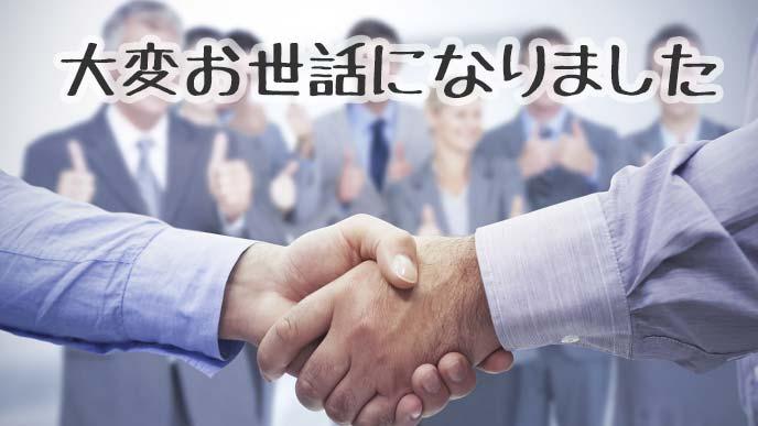 男性2人の握手とスタッフたち