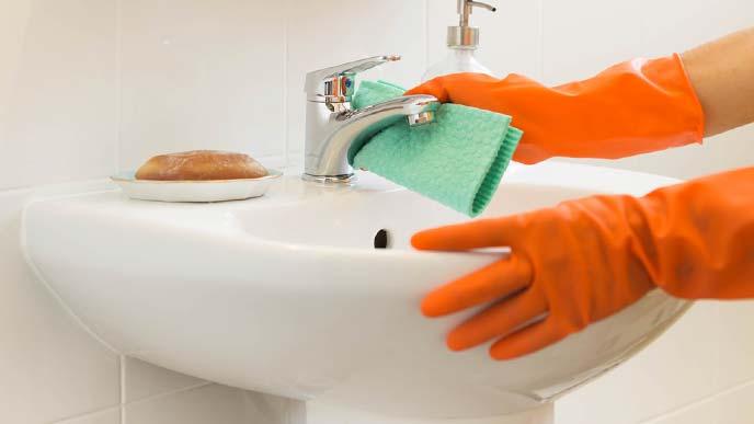 オレンジ色の手袋で洗面台を拭いている様子
