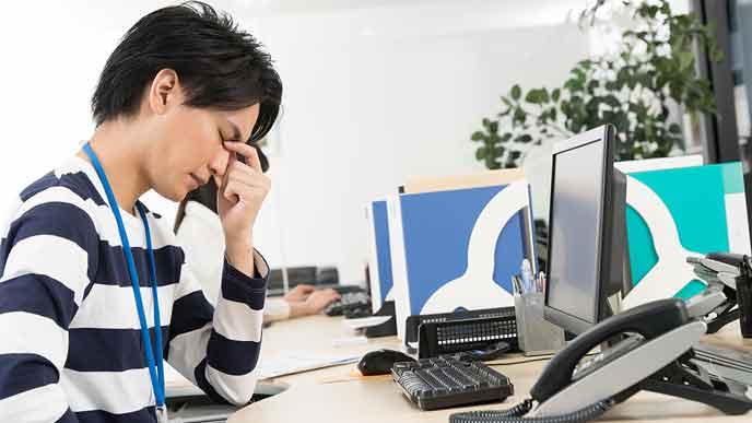 デスクの前で目を閉じて疲れをとる男性