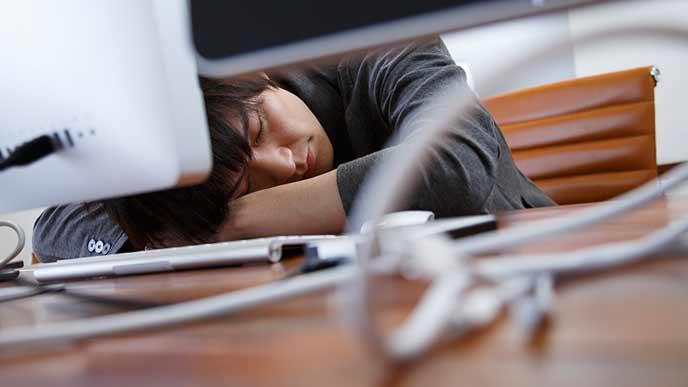 机に伏せて仮眠をとる男性