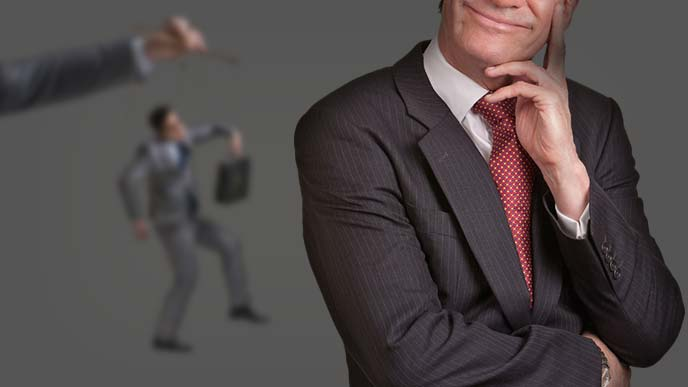 操り人形な男性をバックにダークにほくそ笑む男性