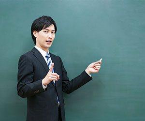 黒板の前に立つ男の人