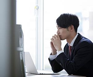 ノートパソコンの前に座って考える男性社員