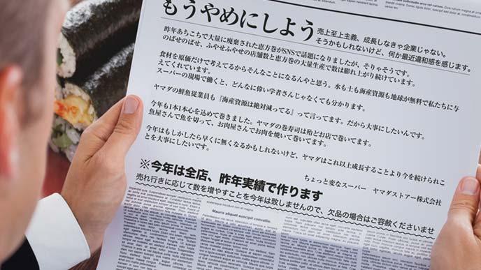 もうやめにしようの新聞広告を読んでいる男性